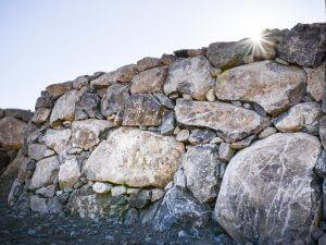 boulder retaining wall with sunlight splashing through the top