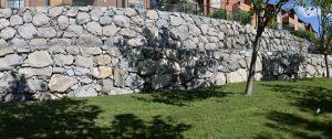 large multi-tier retaining wall set above freshly green grass alongside trees